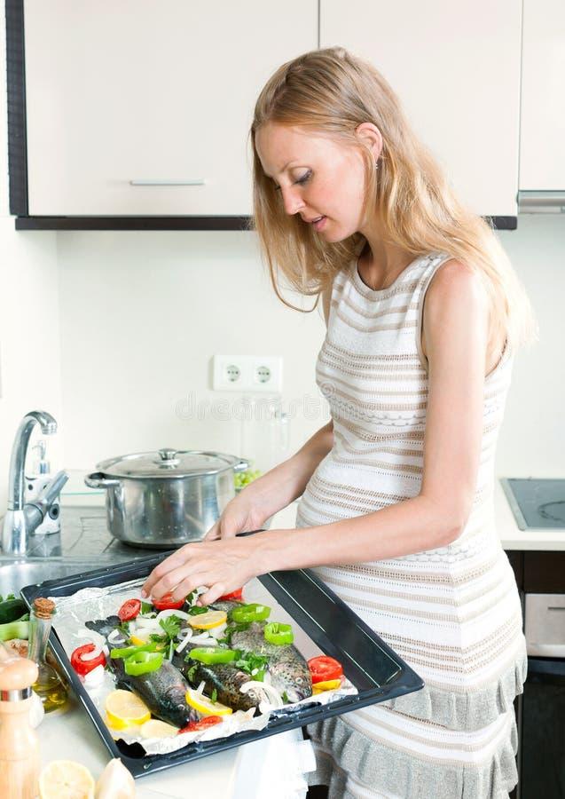 Mulher que cozinha peixes da truta na bandeja fotografia de stock