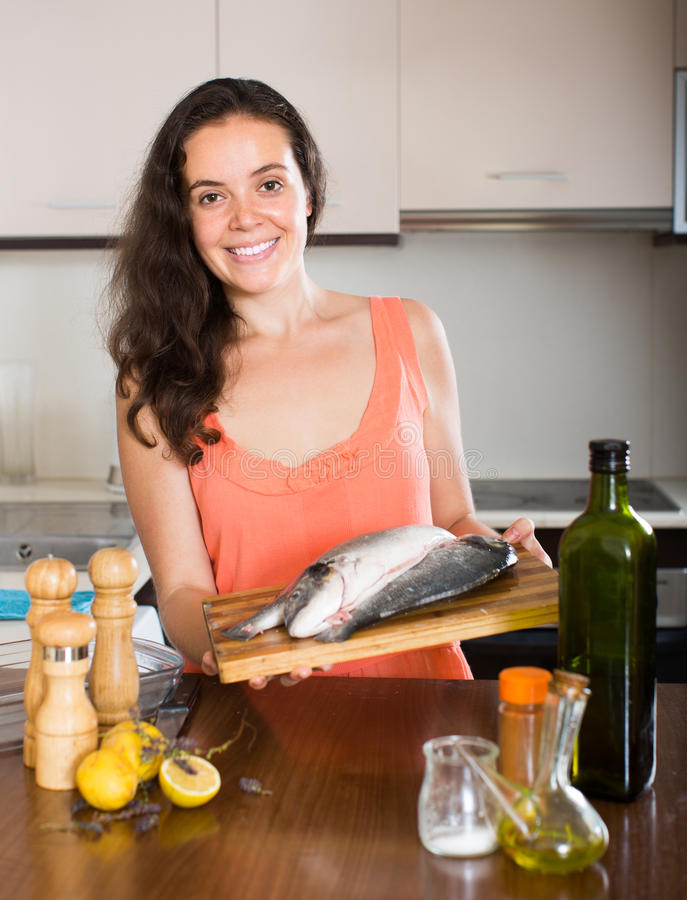 Mulher que cozinha peixes na cozinha fotografia de stock royalty free