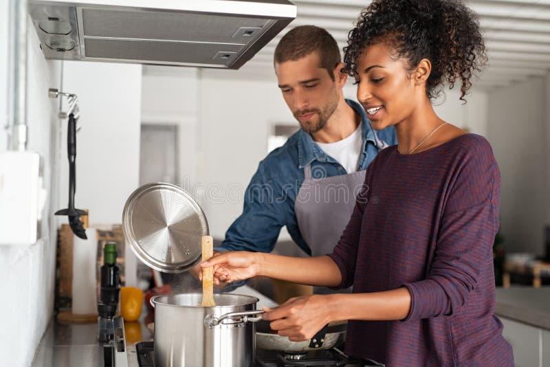 Mulher que cozinha a refeição com seu noivo imagens de stock royalty free