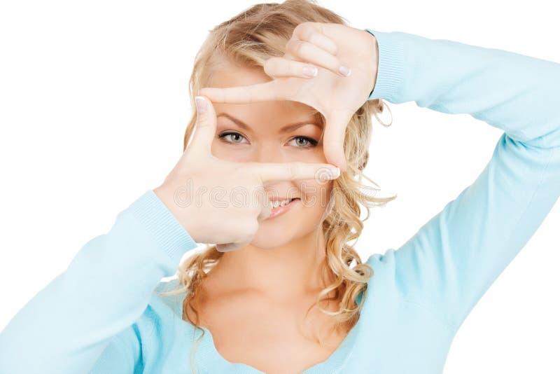 Mulher que cria um quadro com os dedos ou o instantâneo imagem de stock royalty free