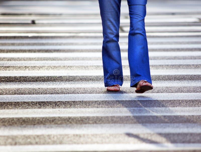 Mulher que cruza a rua imagens de stock