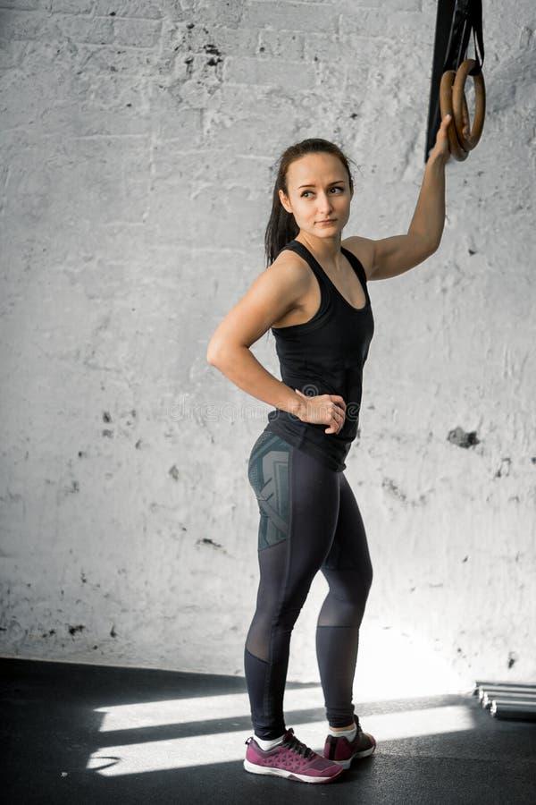 Mulher que dá certo com anéis ginásticos no gym apto da cruz fotos de stock