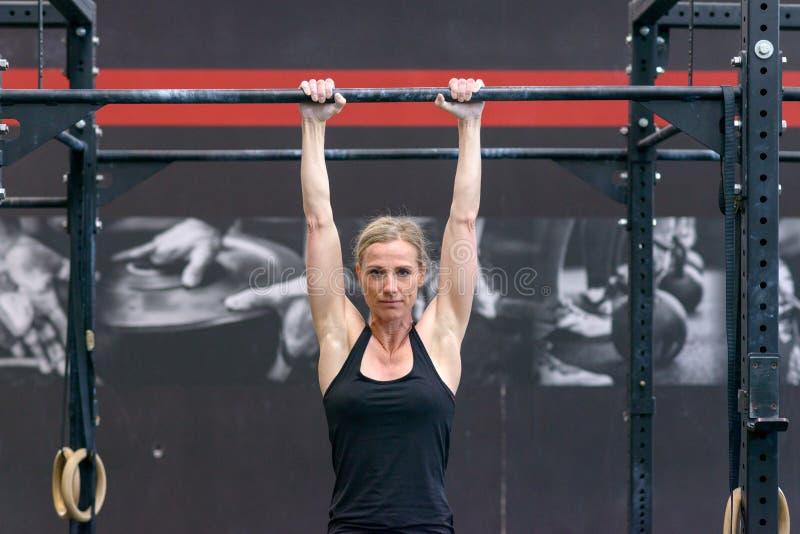Mulher que dá certo em barras transversais em um gym imagem de stock royalty free