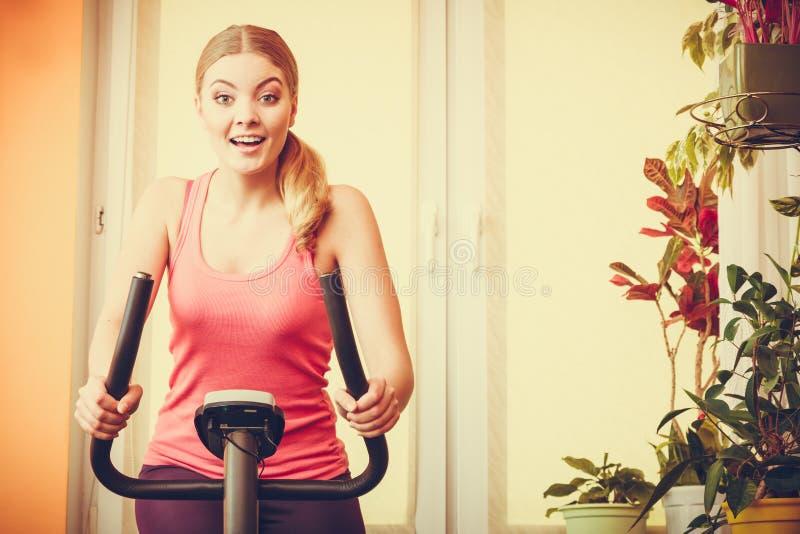 Mulher que dá certo na bicicleta de exercício Aptidão imagem de stock
