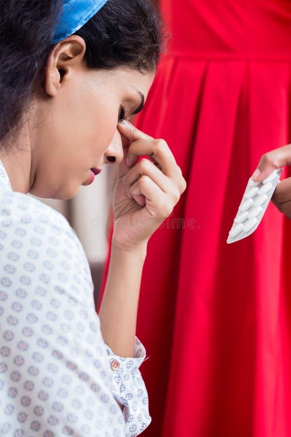 Mulher que dá a medicamentação contra a dor de cabeça imagem de stock royalty free
