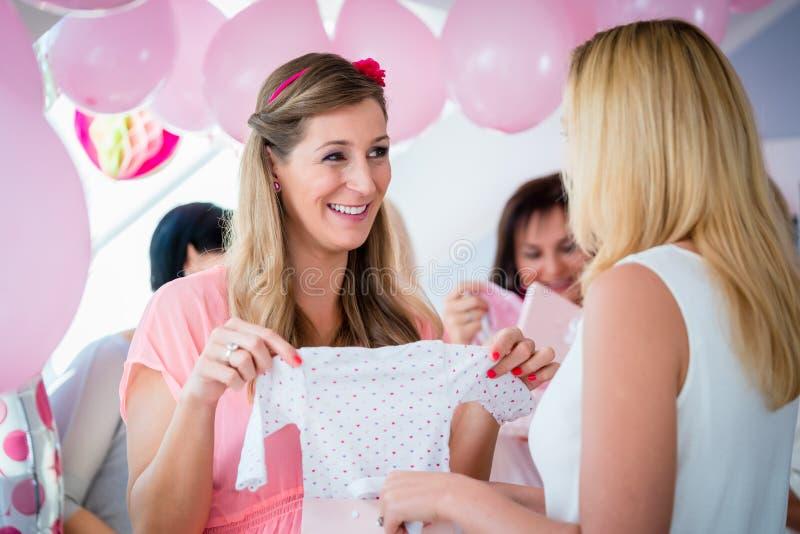 Mulher que dá o presente ao amigo grávido na festa do bebê foto de stock royalty free