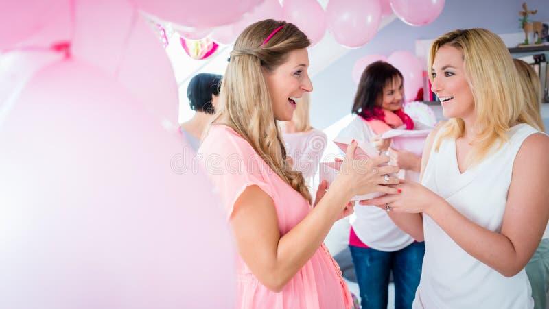 Mulher que dá o presente ao amigo grávido na festa do bebê imagem de stock