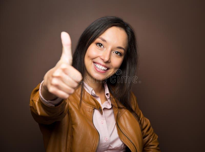 A mulher que dá os polegares levanta o sorriso do gesto do sinal da mão da aprovação fotos de stock