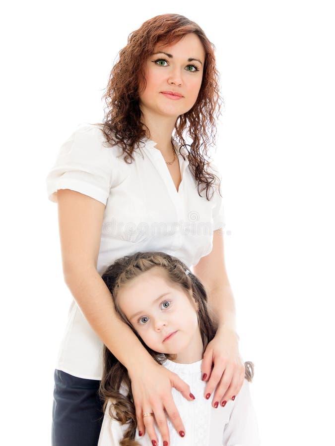 Mulher que dá um abraço a sua filha pequena. fotos de stock royalty free