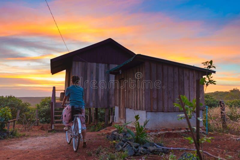 Mulher que dá um ciclo no campo, cabine de madeira, céu dramático no por do sol, desejo por viajar de viagem, fora atividades foto de stock royalty free