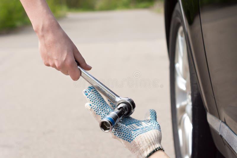 Mulher que dá a um mecânico uma chave inglesa do soquete fotos de stock