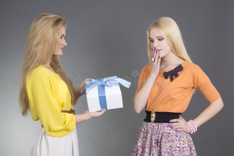 Mulher que dá um presente a seu amigo surpreendido foto de stock royalty free