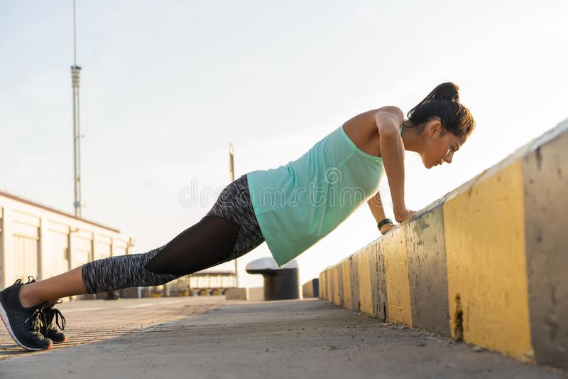 A mulher que da aptidão fazer empurra levanta o verão exterior do exercício do treinamento que nivela o estilo de vida saudável d imagens de stock royalty free