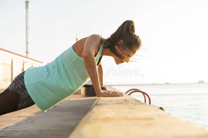 A mulher que da aptidão fazer empurra levanta o verão exterior do exercício do treinamento que nivela o estilo de vida saudável d fotos de stock