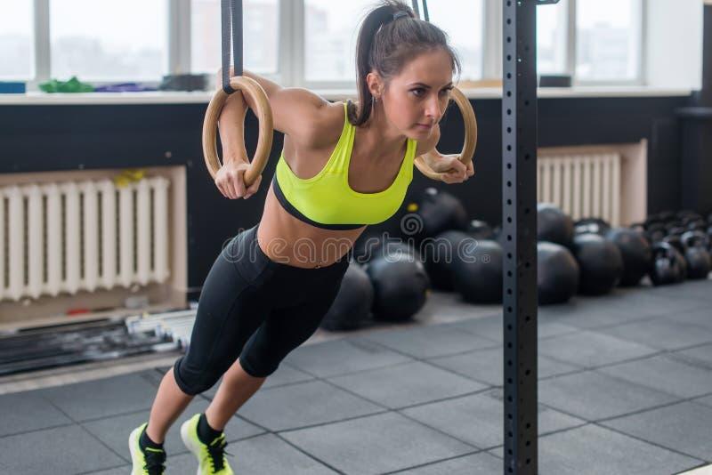 A mulher que da aptidão fazer empurra levanta os braços do treinamento com anéis da ginástica no esporte saudável do estilo de vi imagens de stock