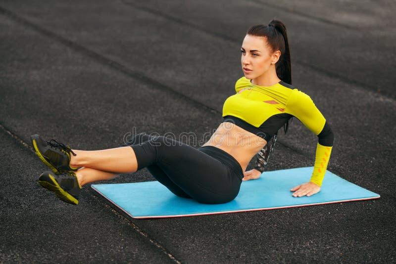 A mulher que da aptidão fazer se senta levanta em dar certo do estádio Menina desportiva que exercita os abdominals, exteriores imagem de stock