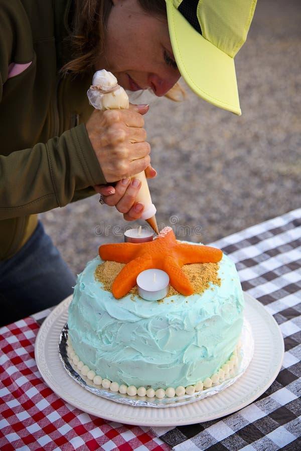 Mulher que decora o bolo ao ar livre foto de stock