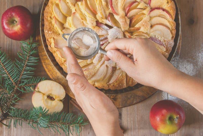 Mulher que decora a torta de maçã, tonificada foto de stock royalty free