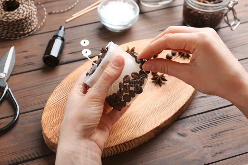 Mulher que decora a vela feito a mão com os feijões de café na tabela de madeira imagens de stock royalty free
