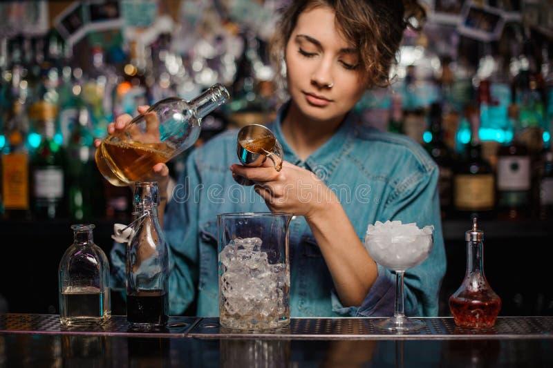 A mulher que derrama ao copo de vidro da medição com gelo cuba uma bebida alcoólica do jigger imagem de stock royalty free