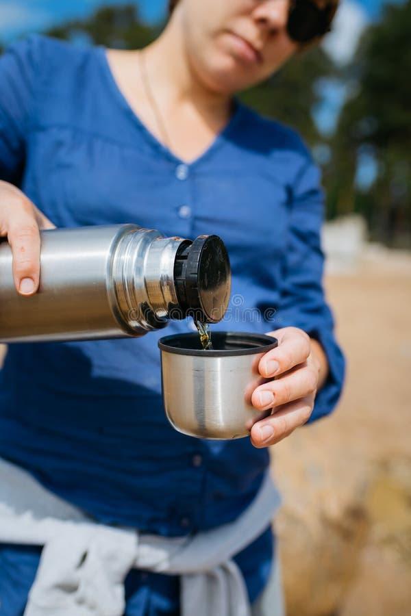 Mulher que derrama o chá quente de uma garrafa térmica em um Sandy Beach em um dia ensolarado Fim acima imagens de stock