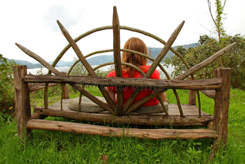 Mulher que descansa em um grande banco de madeira imagens de stock royalty free