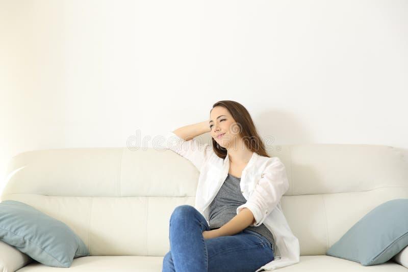 Mulher que descansa em um sofá com espaço da cópia acima fotografia de stock royalty free