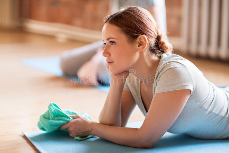 Mulher que descansa na esteira da ioga no gym ou no estúdio imagens de stock