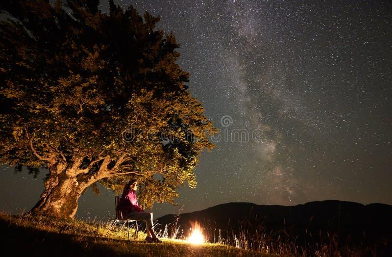 Mulher que descansa na noite que acampa nas montanhas sob o c?u estrelado foto de stock royalty free