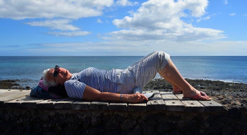 Mulher que descansa no sol na parede com o oceano no fundo foto de stock