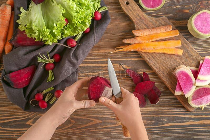 Mulher que descasca a beterraba madura sobre a tabela de madeira, vista superior imagem de stock royalty free