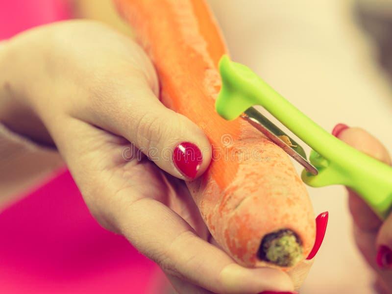 Mulher que descasca o vegetal da cenoura imagens de stock
