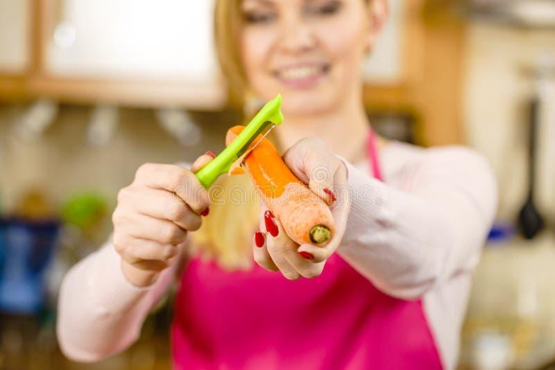 Mulher que descasca o vegetal da cenoura foto de stock royalty free