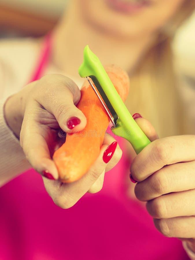 Mulher que descasca o vegetal da cenoura imagens de stock royalty free