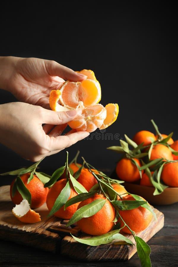 Mulher que descasca a tangerina madura sobre a tabela no fundo escuro imagem de stock royalty free