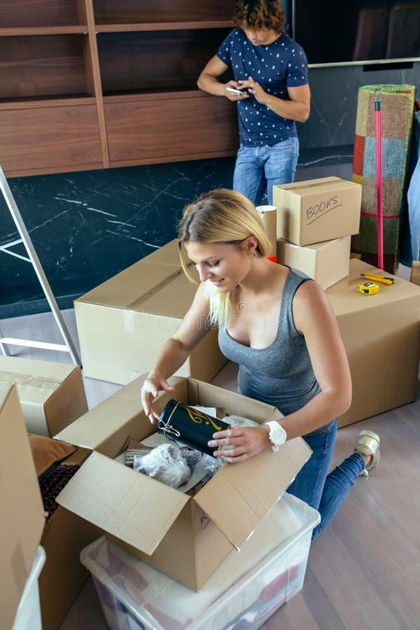 Mulher que desembala caixas moventes fotografia de stock