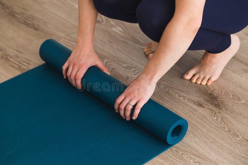 Mulher que desenrola a esteira da ioga em um estúdio da ioga fotografia de stock