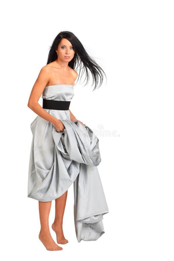 A mulher que desgasta o vestido de prata longo está na ponta do pé fotos de stock royalty free