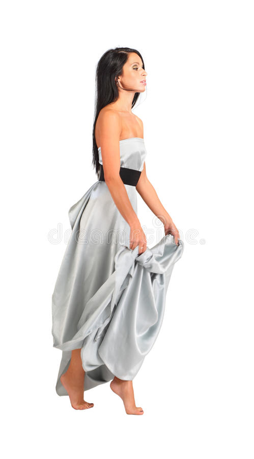 A mulher que desgasta o vestido de prata longo vai na ponta do pé imagens de stock royalty free