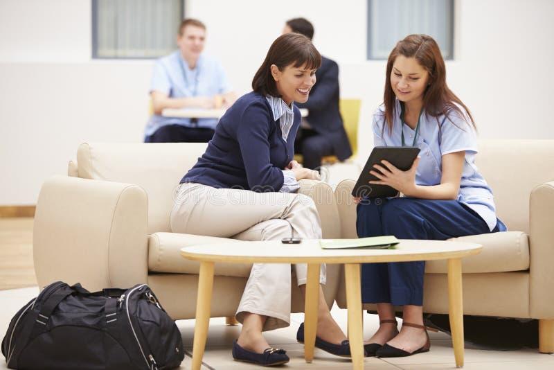 Mulher que discute resultados com a enfermeira On Digital Tablet imagem de stock royalty free