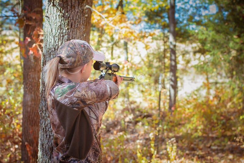 Mulher que dispara em um rifle fotografia de stock