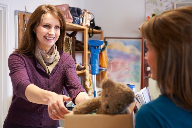 Mulher que doa artigos indesejáveis à loja da caridade foto de stock royalty free