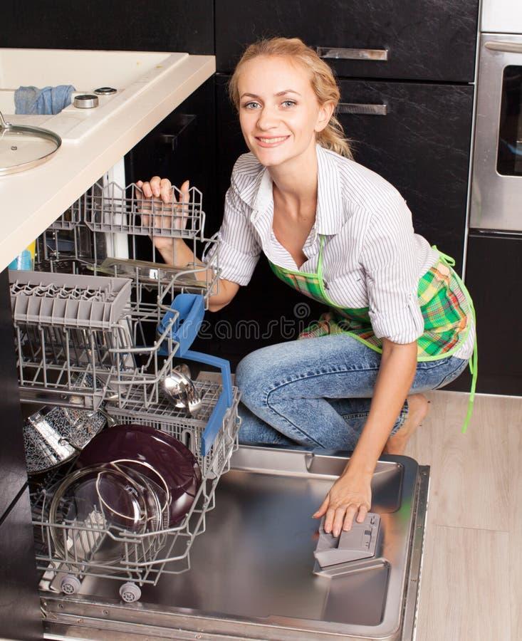 Mulher que dobra os pratos na máquina de lavar louça imagens de stock