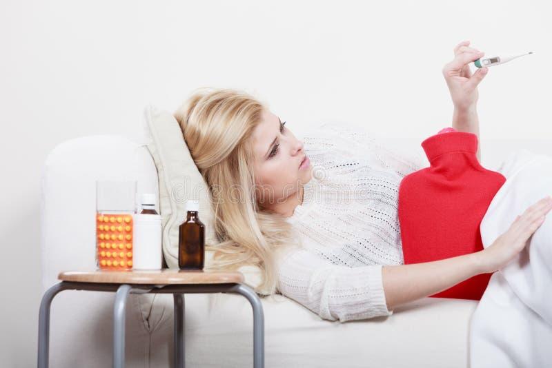 Mulher que ? doente estando com a gripe que encontra-se no sof? imagem de stock royalty free