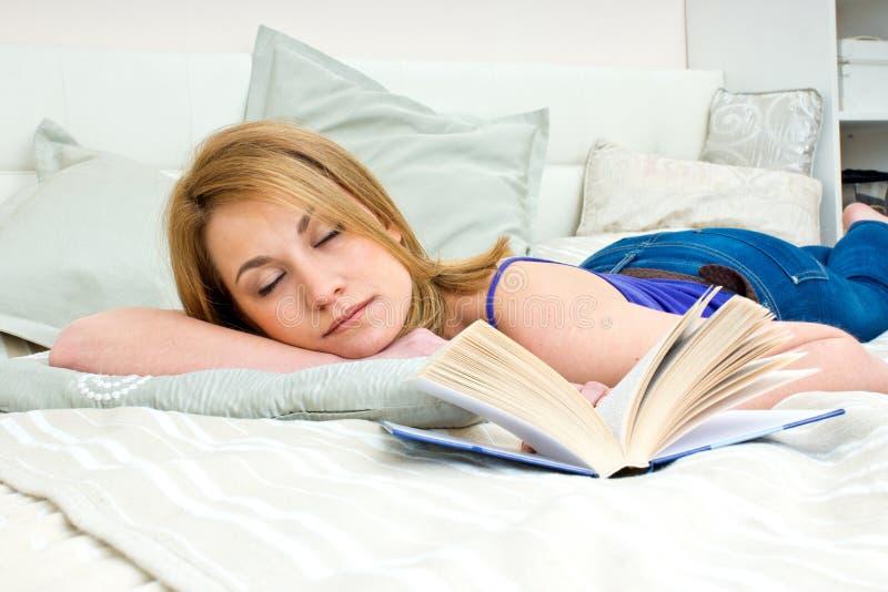 Mulher que dorme com livro foto de stock