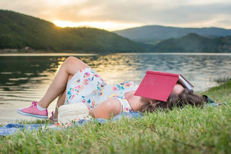 Mulher que dorme com um livro pelo lago Abrandamento de solo foto de stock