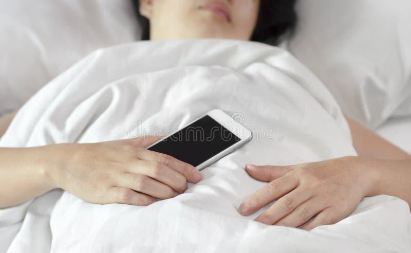 Mulher que dorme e que guarda um telefone celular foto de stock