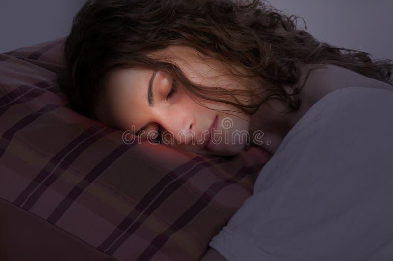 Mulher que dorme em um descanso vermelho fotografia de stock royalty free