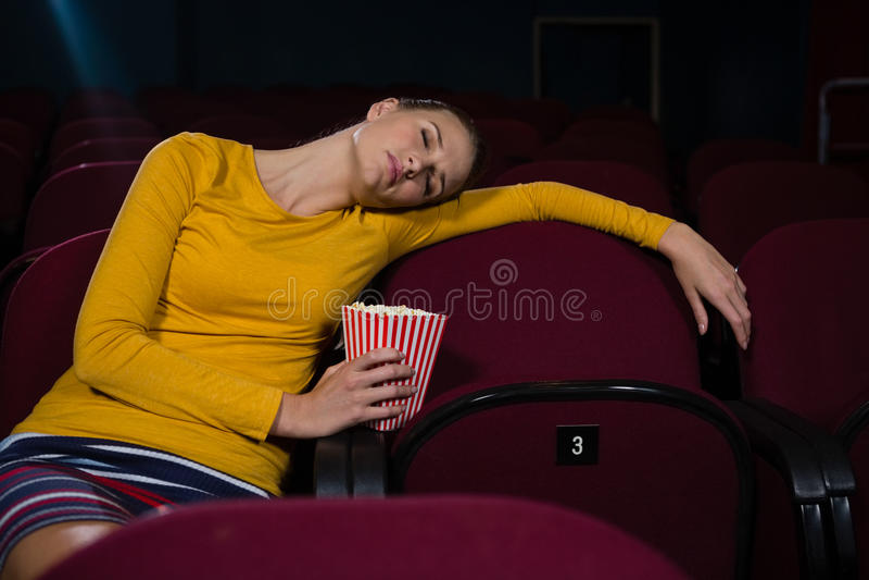 Mulher que dorme em um teatro de filme imagem de stock