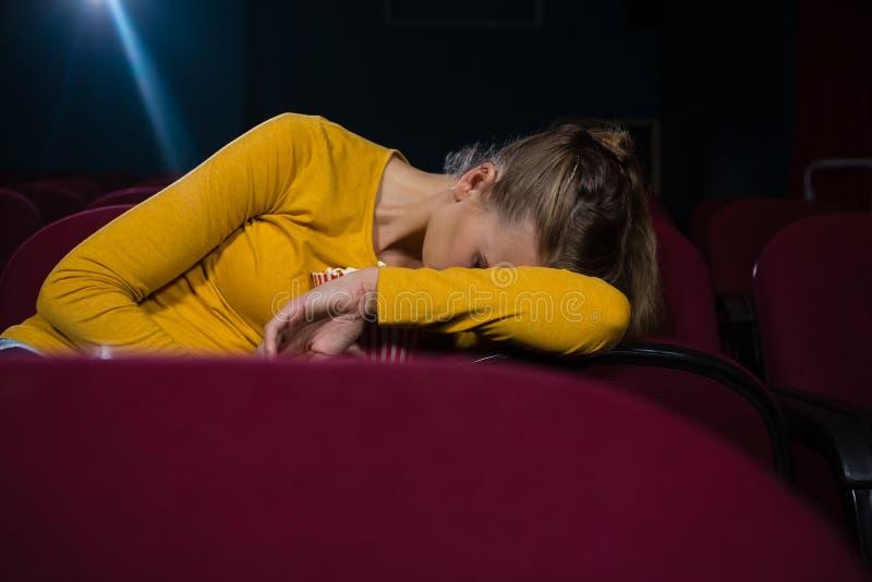 Mulher que dorme em um teatro de filme foto de stock royalty free